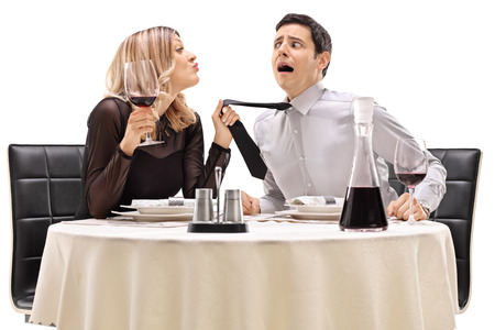 intrusive: Drunk woman pulling her date by his tie and trying to kiss him isolated on white background
