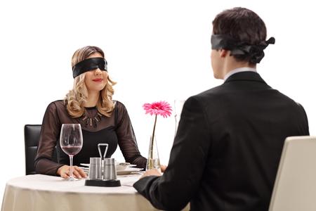 Jonge man en vrouw zittend op een blind date in een restaurant op een witte achtergrond Stockfoto