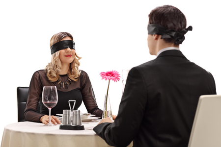 Junger Mann und Frau, die auf einem Blind Date in einem Restaurant auf weißem Hintergrund sitzt Standard-Bild