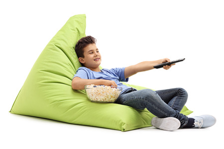 changing channels: Little kid changing channels on TV and eating popcorn seated on a green beanbag isolated on white background Stock Photo