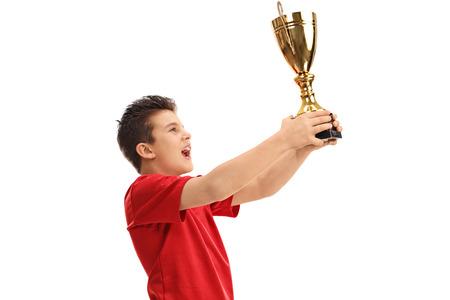 Joyful junior athlete lifting a trophy and celebrating isolated on white background