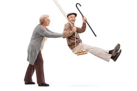 Donna anziana premendo un uomo su un'altalena in legno isolato su sfondo bianco Archivio Fotografico