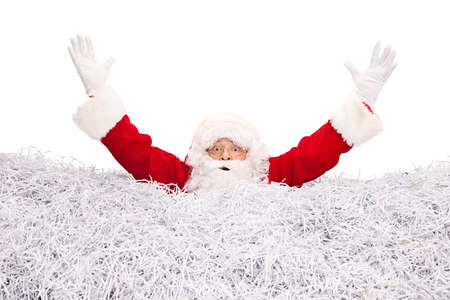 shredded paper: Studio shot of Santa Claus drowning in a pile of shredded paper isolated on white background