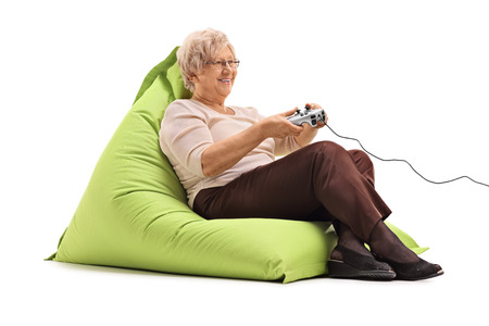 beanbag: Elderly lady playing video games seated on a comfortable green beanbag isolated on white background
