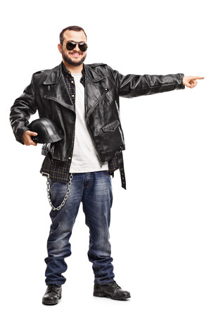 Full length portrait of a young biker in a black leather jacket pointing to the right with his hand