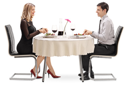 若い男と女が白い背景に分離されたレストランのテーブルに着席している日に食べる