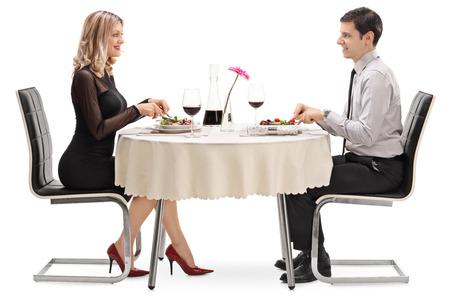 Hombre joven y mujer comiendo en una fecha sentado en una mesa de restaurante aislados sobre fondo blanco Foto de archivo