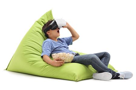 놀라 울 어린 소년 VR 고글에서 찾고 흰색 배경에 고립 된 콩 주머니에 앉아 팝콘을 먹고