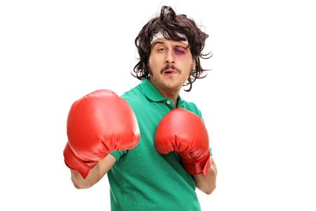 Jeune boxeur avec un oeil au beurre noir et des gants de boxe rouges isolé sur fond blanc