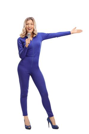 Retrato de cuerpo entero de una mujer en un juego de carreras de una sola pieza azul hablando en micrófono y señalando con la mano hacia la derecha