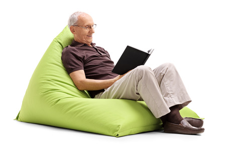 beanbag: Senior gentleman reading a book and relaxing seated on a green beanbag isolated on white background Stock Photo