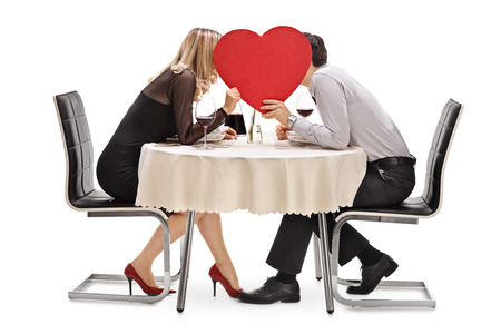 big behind: Young couple kissing behind a big red heart seated on a restaurant table isolated on white background