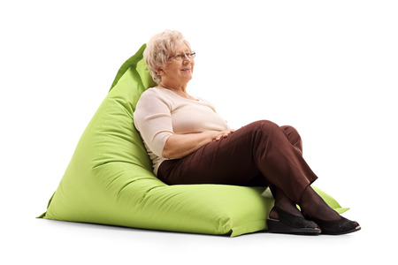 beanbag: Relaxed senior lady sitting on a comfortable green beanbag isolated on white background