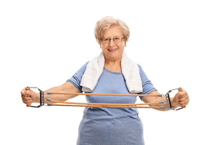 one people: Older woman exercising with a resistance band isolated on white background