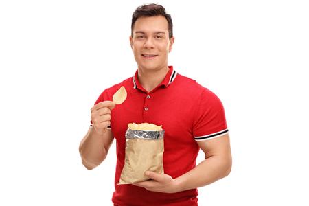 hombre comiendo: Joven alegre comiendo papas fritas y mirando a la cámara aislada en el fondo blanco