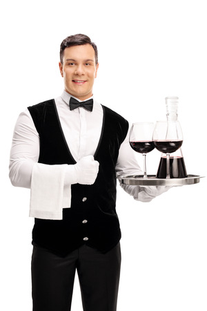 white wine: Vertical shot of a cheerful waiter holding a tray with a bottle of red wine and two glasses isolated on white background
