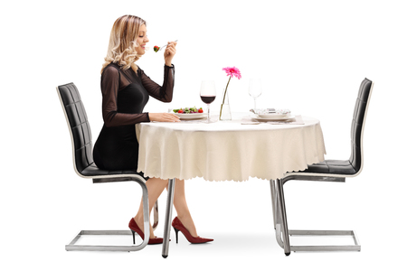 persona sentada: Studio foto de una mujer alegre joven que come una ensalada sentado en una mesa de restaurante aislado en fondo blanco