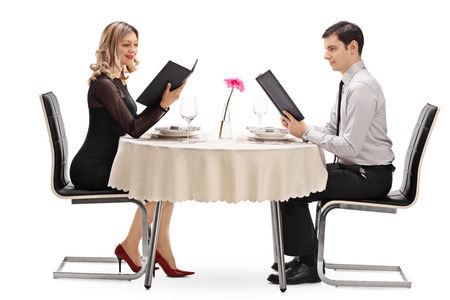 dinner date: Young couple reading the menu and sitting at a restaurant on a date isolated on white background Stock Photo