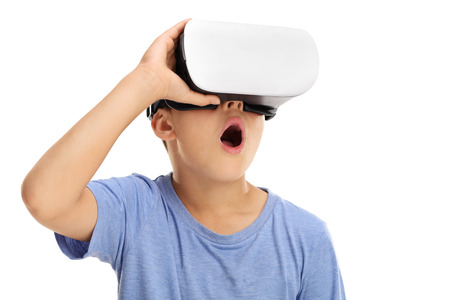 Amazed little boy experiencing virtual reality isolated on white background Stock Photo