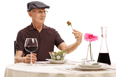 unhappy man: Displeased senior looking at a salad in disgust seated at a restaurant table isolated on white background