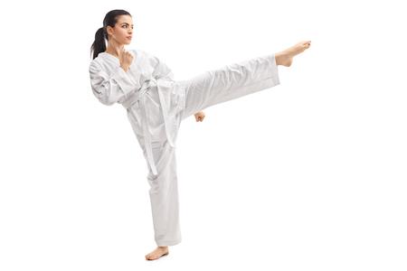 Studio shot di una giovane donna, praticando arti marziali in kimono bianco isolato su sfondo bianco