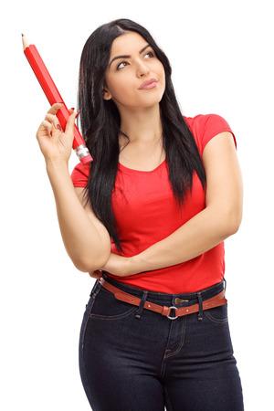 mujer sola: Tiro vertical de una mujer joven pensativo que sostiene un lápiz enorme aislado en el fondo blanco Foto de archivo