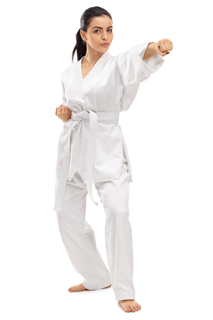 martial artist: Full length portrait of a young female martial artist punching isolated on white background