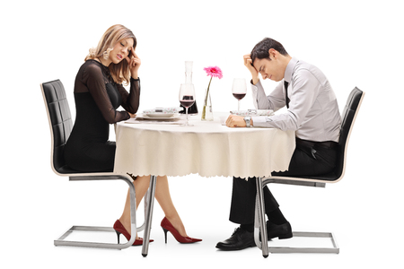 breaking up: Young couple sitting at a table and arguing with each other isolated on white background