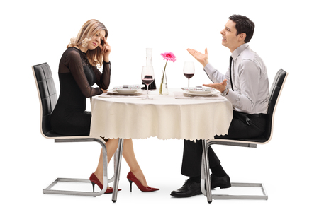 breaking up: Young woman breaking up with her boyfriend seated at a restaurant table isolated on white background Stock Photo