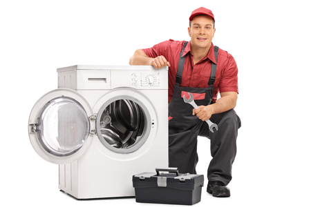 Young repairman holding a wrench and posing next to a broken washing machine isolated on white background