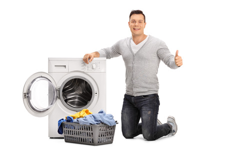 emptying: Cheerful guy doing laundry and giving a thumb up isolated on white background
