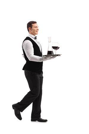 persona caminando: Tiro lleno perfil longitud de un joven camarero con una bandeja con vino y dos copas aisladas sobre fondo blanco Foto de archivo