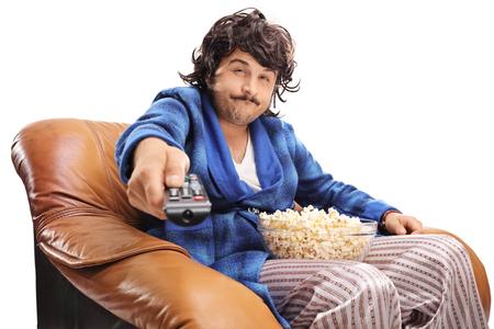 Bored jonge man zittend op een stoel en het veranderen van de kanalen op TV op een witte achtergrond