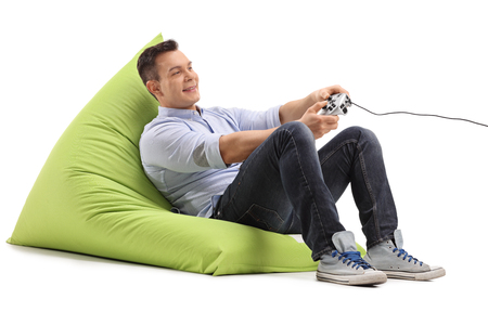 beanbag: Joyful young man playing video games seated on a green beanbag isolated on white background
