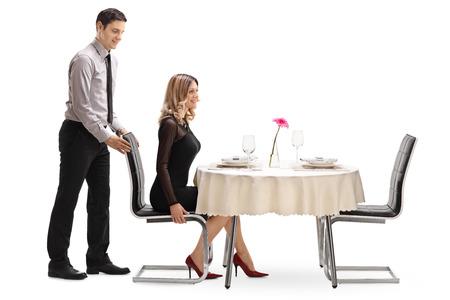 Caballero joven ayuda a su novia con la silla en una mesa de restaurante aislado en fondo blanco Foto de archivo - 58307044