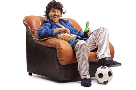 watching football: Joyful man watching football on TV seated in an armchair and eating popcorn isolated on white background