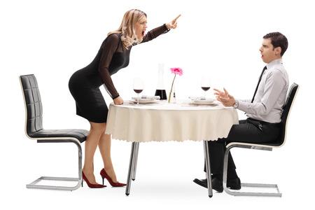 novios enojados: Mujer enojada gritando a su novio sentado en una mesa de restaurante en una fecha aislado en el fondo blanco Foto de archivo