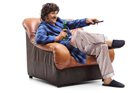 changing channels: Young man sitting in an armchair with a beer in his hand and changing channels on TV isolated on white background