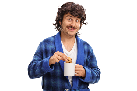 Man holding a cup of milk and dipping a chocolate chip cookie in it isolated on white background Stock Photo