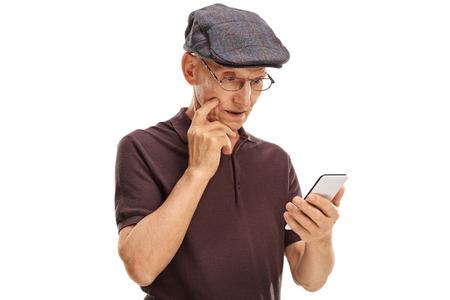 persona mayor: Confundido caballero mayor que mira su teléfono celular aislado en el fondo blanco Foto de archivo