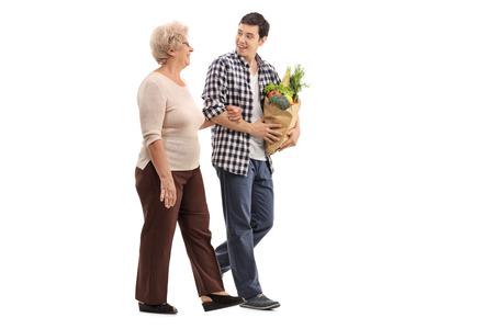 그녀의 식료품 흰색 배경에 고립 된 수석 여자를 돕는 젊은 남자