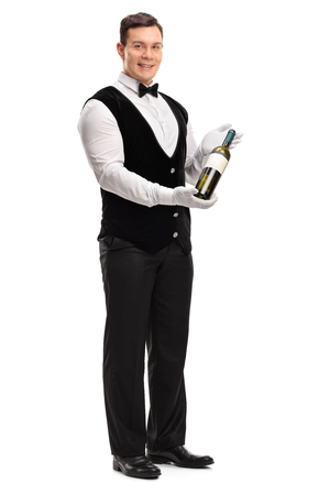 wine background: Full length portrait of a professional waiter holding a bottle of white wine isolated on white background