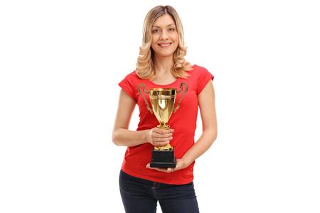 trofeo: Mujer alegre celebración de un trofeo de oro y mirando a la cámara aislada en el fondo blanco
