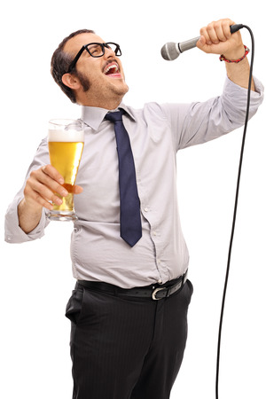 pilsner beer glass: Dedicated man singing on a microphone and holding a pint of beer isolated on white background
