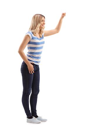 De volledige lengte profiel shot van een jonge blonde vrouw kloppen op de deur op een witte achtergrond