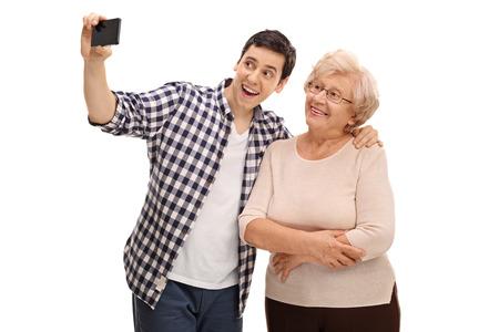 Junger Mann und seine Großmutter selfie mit Handy nehmen isoliert auf weißem Hintergrund Standard-Bild - 58593421