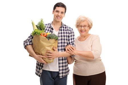 흰색 배경에 고립 된 식료품을 그의 할머니 돕는 손자