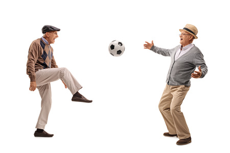 Two joyful senior passing a football and playing isolated on white background