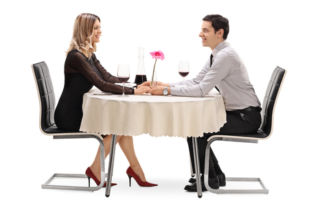 romantic date: Studio shot of a happy couple sitting on a romantic date and looking at each other isolated on white background