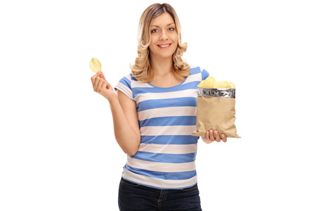 blond girl: Joyful blond woman eating potato chips and looking at the camera isolated on white background Stock Photo
